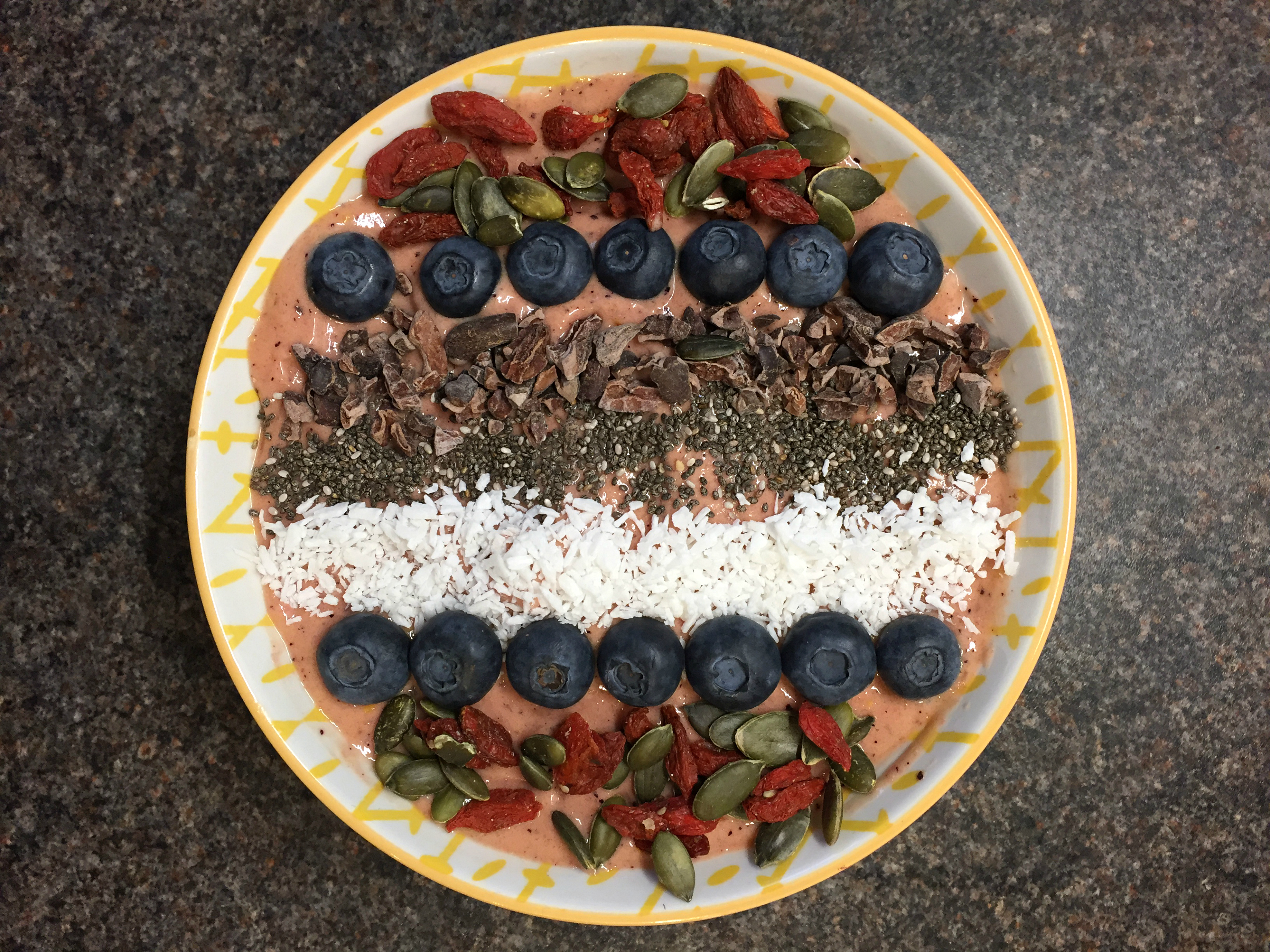 a smoothie bowl topped with coconut blueberries and nuts